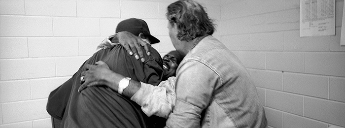 Hospice volunteer Harun Sharif, left, and inmate Calvin Dumas, right, help lift George Alexander out of bed. Sharif and Dumas were helping Alexander get ready for a trip to the hospital in Baton Rouge, LA.